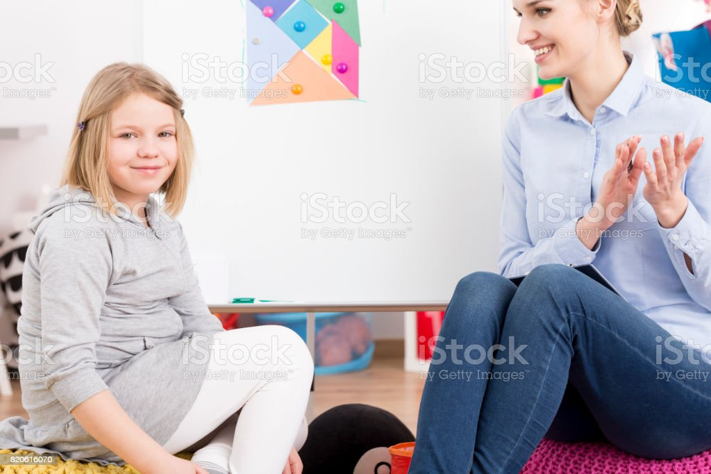 Speech therapist smiling at little girl stock photo