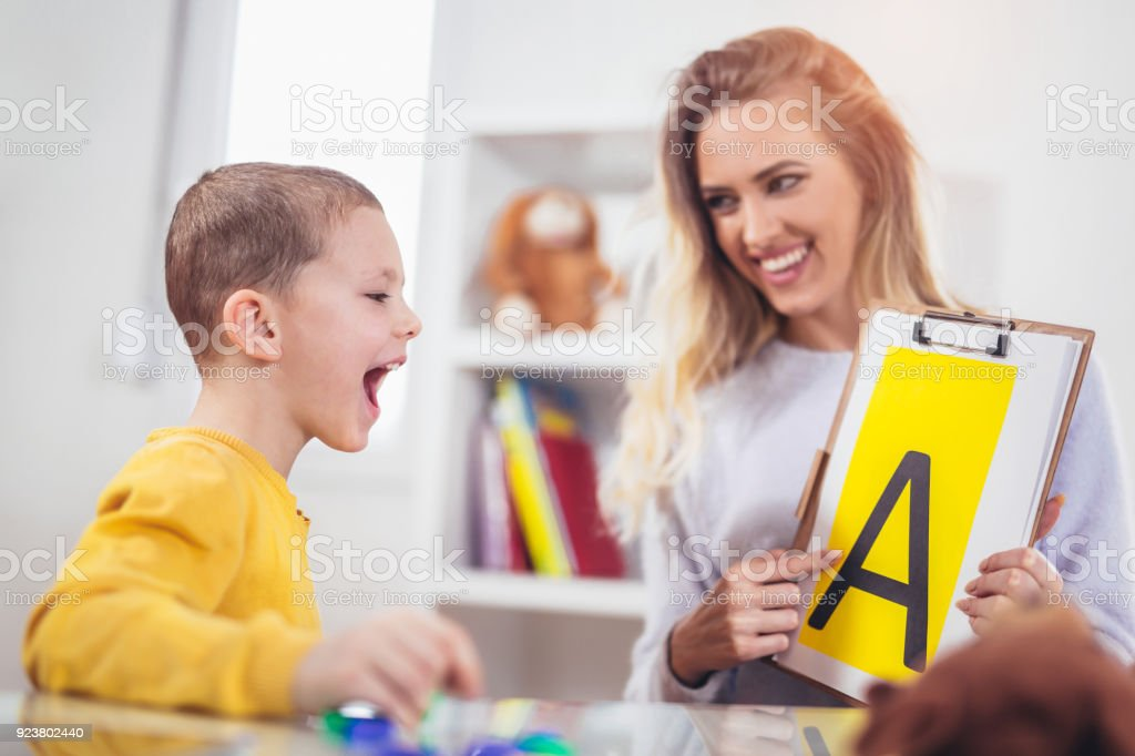 Speech therapist teaches the boys to say the letter A stock photo