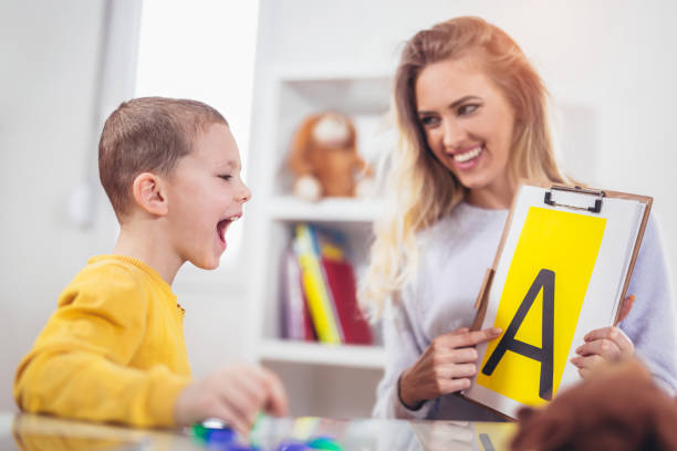 speech therapist teaches the boys to say the letter a - autism stock photos and pictures