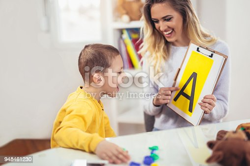 istock Speech therapist teaches the boys to say the letter A 948461230