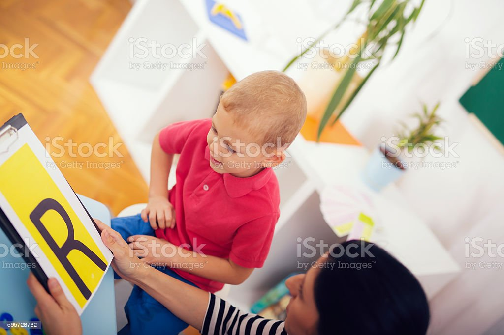 Speech therapist teaches the boys to say the letter R stock photo