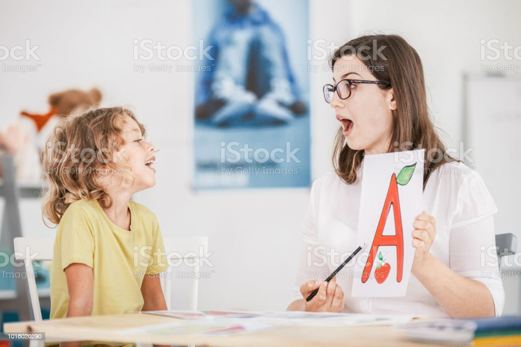 Speech therapist working with a child on a correct pronunciation using a prop with a letter 'a' picture. stock photo