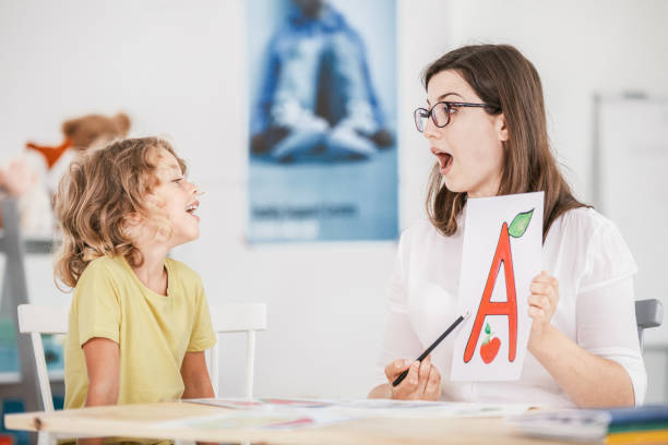 Speech therapist working with a child on a correct pronunciation using a prop with a letter 'a' picture. Speech therapist working with a child on a correct pronunciation using a prop with a letter 'a' picture. speech stock pictures, royalty-free photos & images