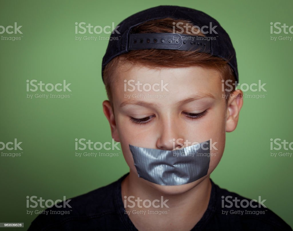 Speechless Boy with Duct Tape Over Mouth stock photo