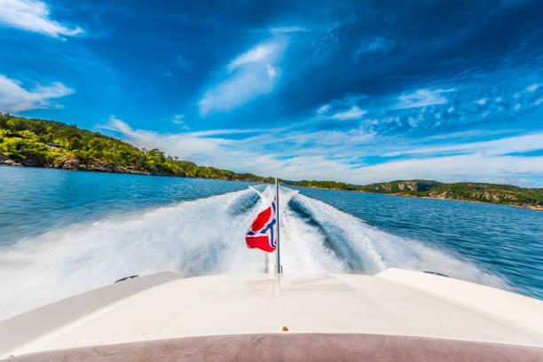schnellboot überquert schnell einen sonnigen fjord mit der norwegischen flagge. - norwegen fahne stock-fotos und bilder