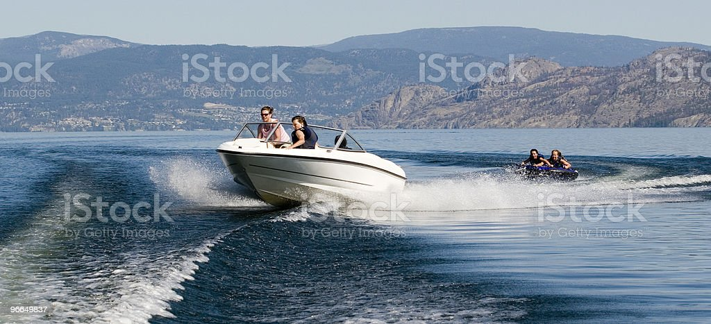 Speed boat with two people on a tube behind it on a lake stock photo