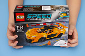 Tambov, Russian Federation - March 04, 2015 LEGO Speed Champions box with McLaren P1 in child's hands. Studio shot.