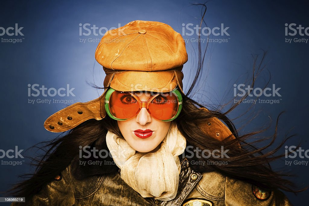 One beautiful woman pilot. She is wearing a leather jacket and cap...