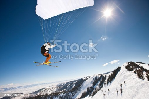 Extreme sports. Action shot of a speed flyer zooming past, high above a mountain peak towards the sun.