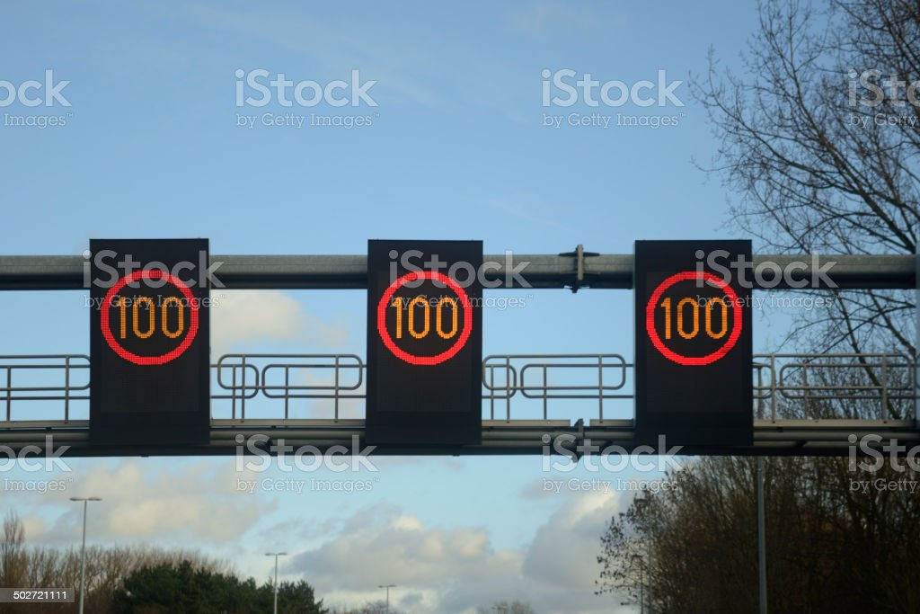 Speed limit 100, three traffic signs, blue sky and clouds stock photo