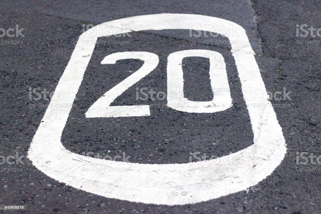speed limit 20mph or kph painted on the road stock photo