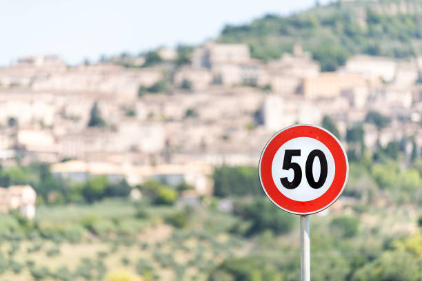 speed limit red 50 kilometers per hour km sign with bokeh background of town or village city of assisi in umbria, italy cityscape during sunny summer day - cartello stradale italia km foto e immagini stock