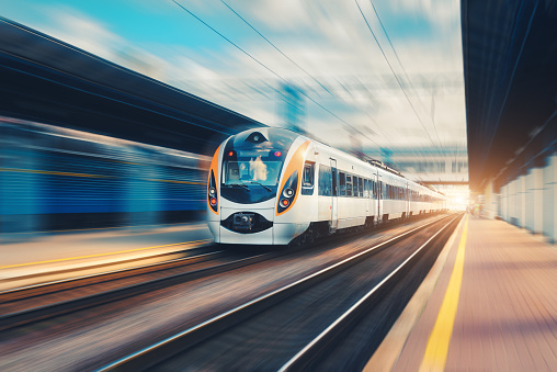 Speed passenger train in motion on the railway station at sunset in Europe. Modern intercity train on railway platform with motion blur effect. Urban scene with railroad. Railway transportation