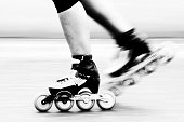 A roller skater is racing down the road, detail of leg and skates.