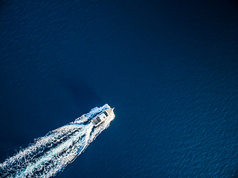 Fast speedboat racing along the open sea leaving white trail. High angle view from drone (quadcopter) Phantom 3.