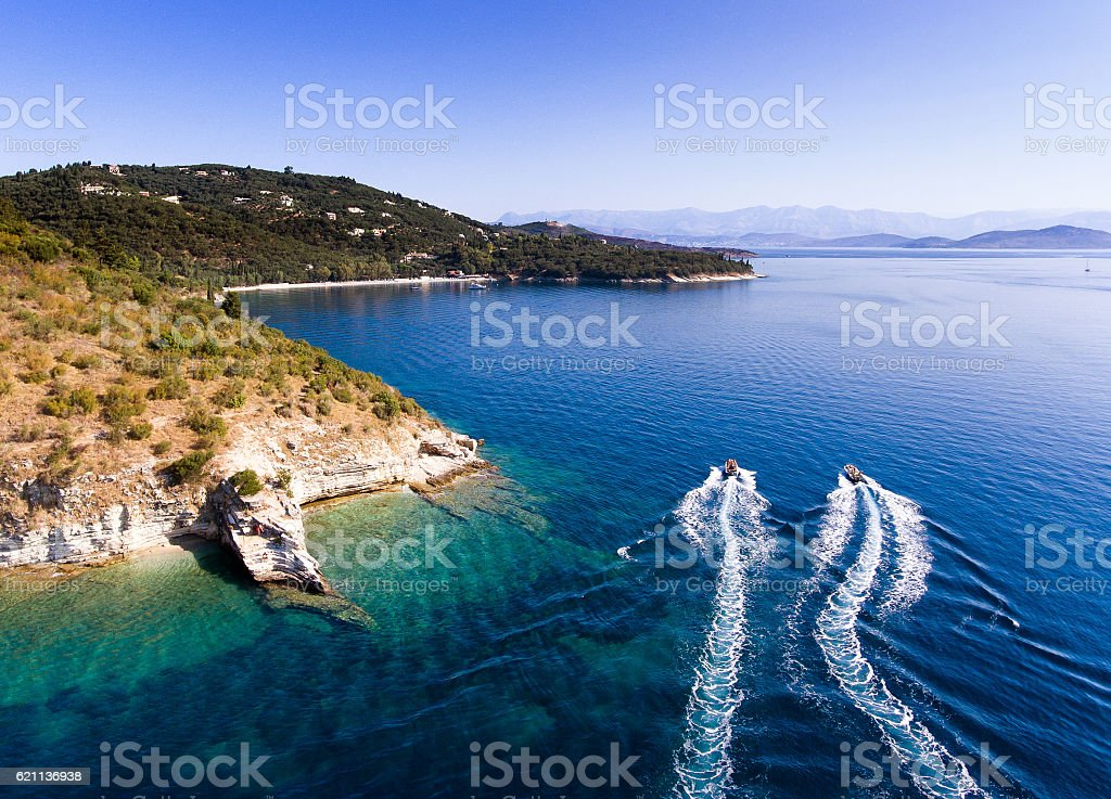 Speedboats navigating past rocky clifs, Corfu island, Kerkyra, G stock photo