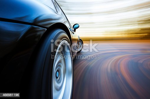 A black sports car turns in to a corner. Autumn leaves are on the road and in the background blur.