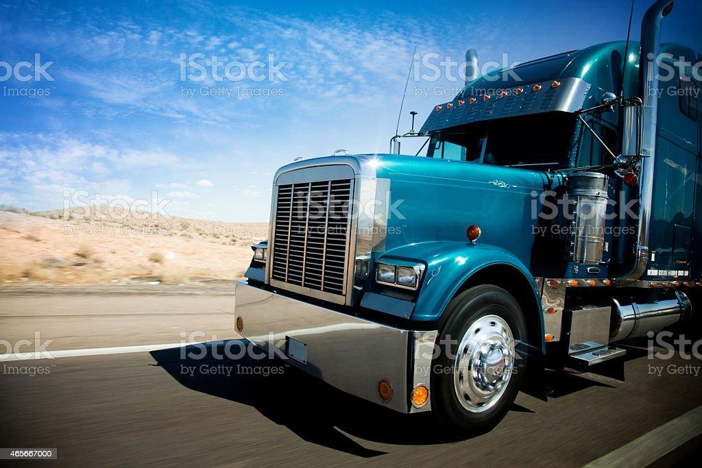 speeding freight truck at sunset light in arizona desert highway stock photo