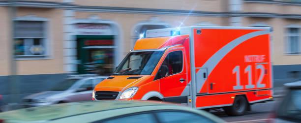 speeding german ambulance - feuerwehrmann deutsch stock-fotos und bilder