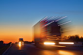 istock Speeding motion blur oncoming trucks with glowing lights after sunset 507477054