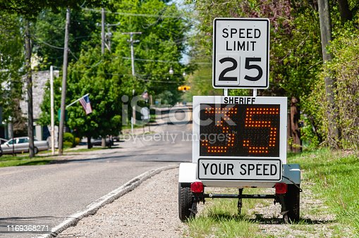 A sheriff's radar device measures the speed of cars passing by.