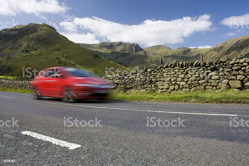 Speeding red car, Lake District National Park stock photo