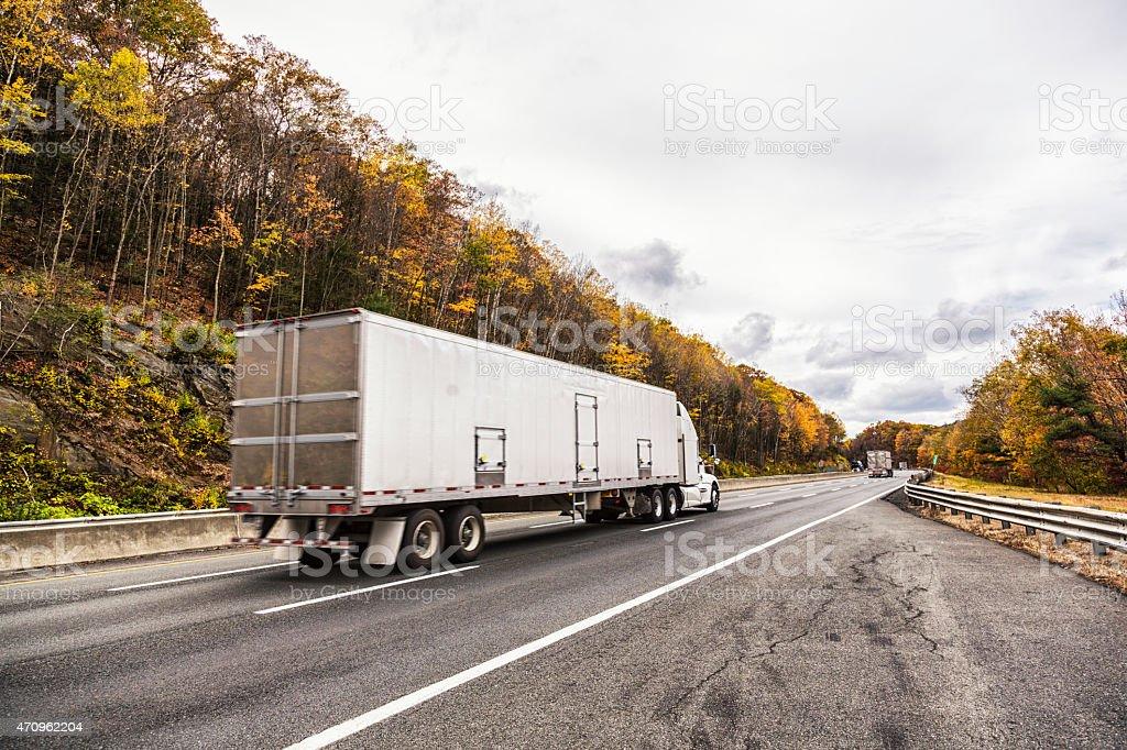 Speeding Trailer Truck Rural Highway Autumn Foliage stock photo