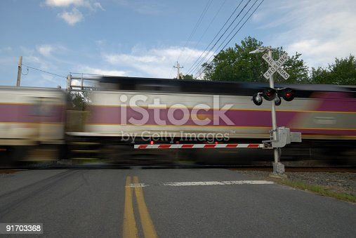 A speeding train going thru a railway crossing.