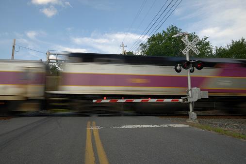 A speeding train going thru a railway crossing.