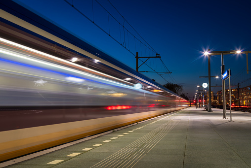 Train passing the platform on a railroad station in the evening. Groningen, Holland.