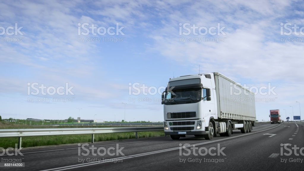 Speeding White Semi Truck with Cargo Trailer Drives on the Highway. Truck is First in the Column of Heavy Vehicles, Sun is Shining. stock photo