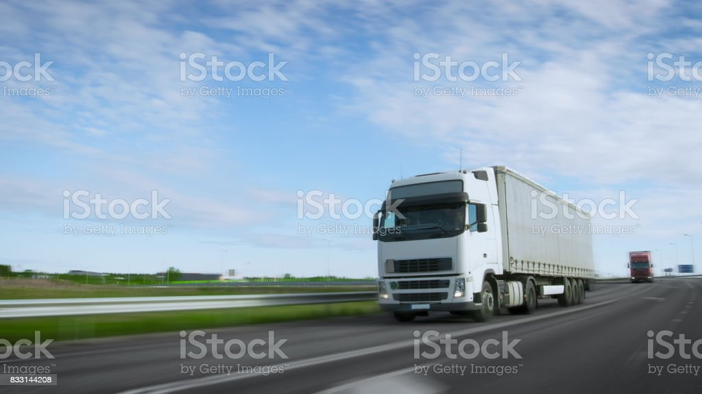 Speeding White Semi Truck with Cargo Trailer Drives on the Highway. Truck is First in the Column of Heavy Vehicles, Sun is Shining. Blur motion. stock photo
