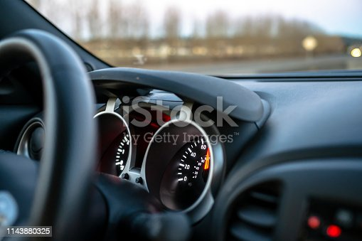 The speedometer of a crossover car with a gray interior with a luminous dial located on the information control panel shows the actual speed of the car on the road, flashing behind the windshield