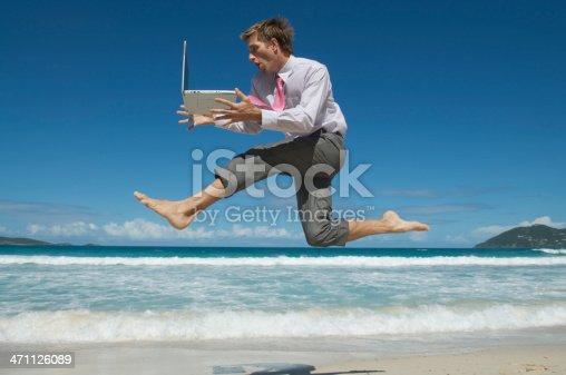 istock Speedy Businessman Jumping with Laptop Across Tropical Beach 471126089