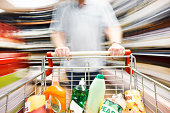 View over filled shopping cart racing towards camera down a supermarket aisle, pushed at speed by an out-of-focus man and showing extreme, motion blur and distortion along the shelves.