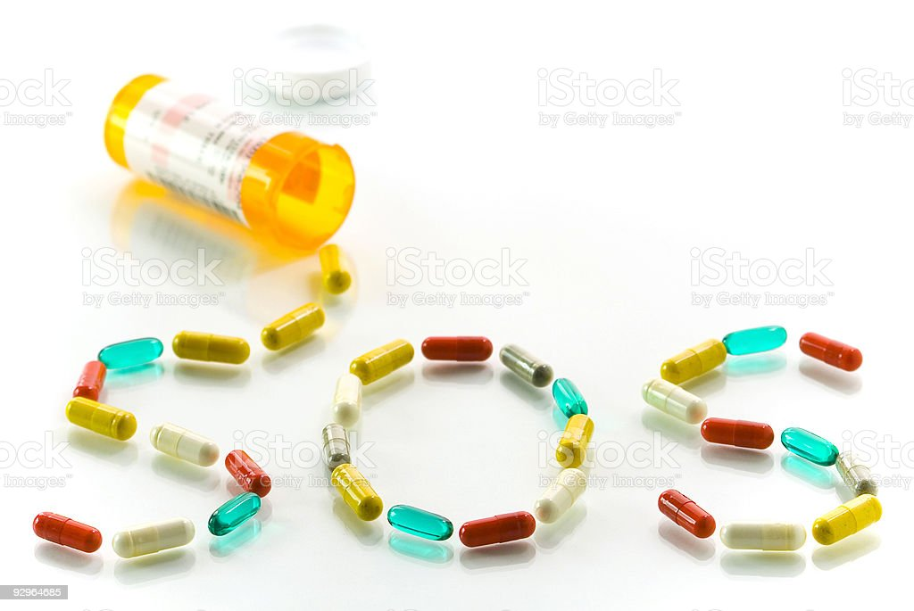 SOS spelled out of pills as if they fell out of a bottle royalty-free stock photo