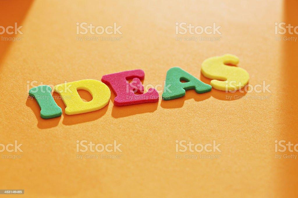 IDEAS spelled out on orange background:inspiration strikes! royalty-free stock photo