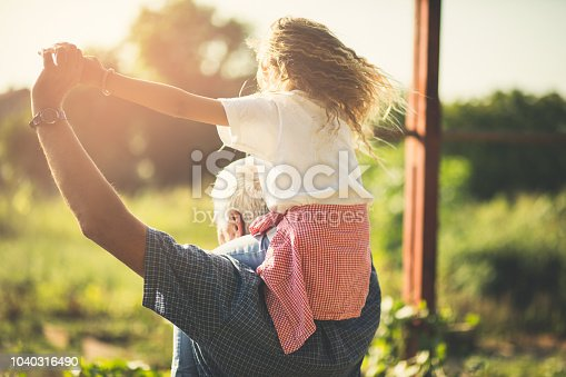 Spend your retirement days with your granddaughter. Grandfather and granddaughter spending time together in nature. Carrying on shoulders. Copy space.