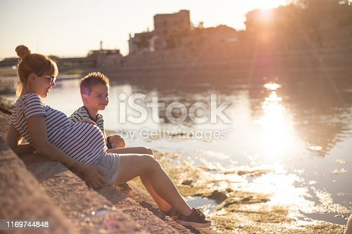 Young pregnant woman siting by the river and enjoying with her five years old son.