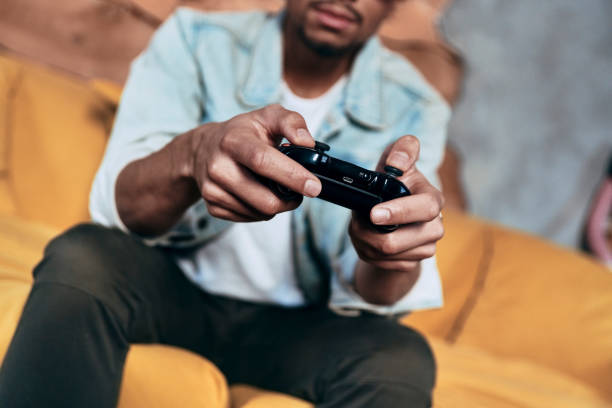 Spending carefree time. Close up of young man in casual clothing playing video games while spending time at home man cave couch stock pictures, royalty-free photos & images