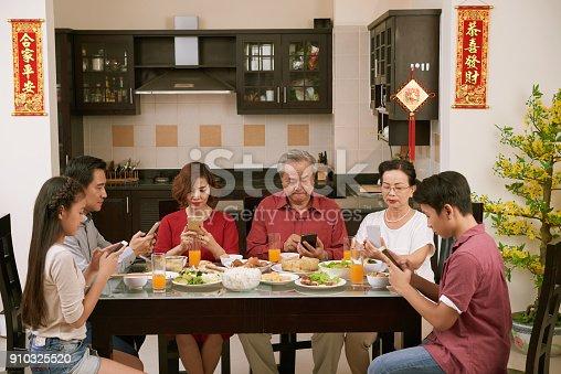 istock Spending family dinner in smartphones 910325520