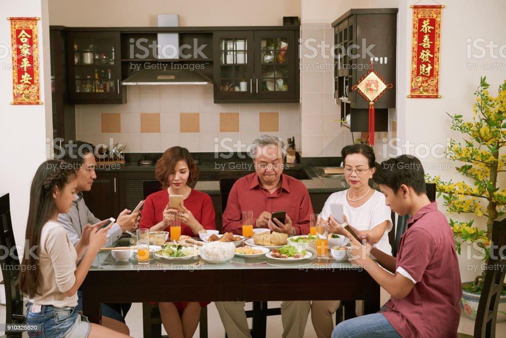 Spending family dinner in smartphones stock photo