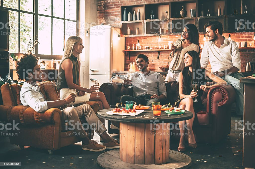 Spending great time with best friends. Group of cheerful young people enjoying food and drinks while spending nice time in comfortable chairs on the kitchen together Adult Stock Photo