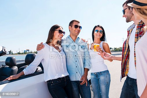 Group of young happy people talking to each other and smiling while standing near their convertible