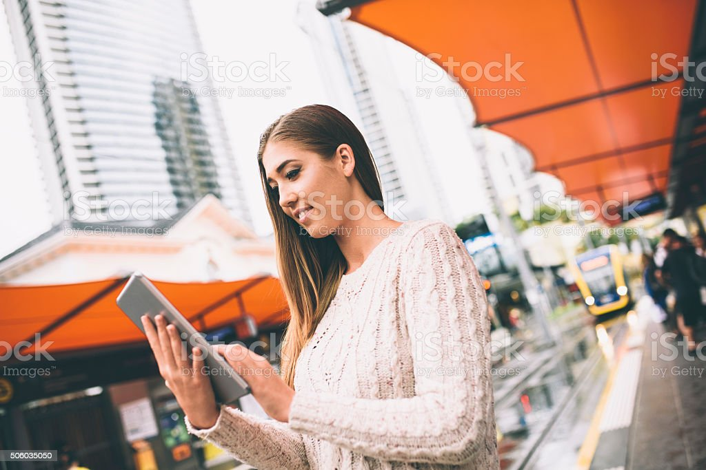 Beautiful young woman standing on a tram station and using digital...