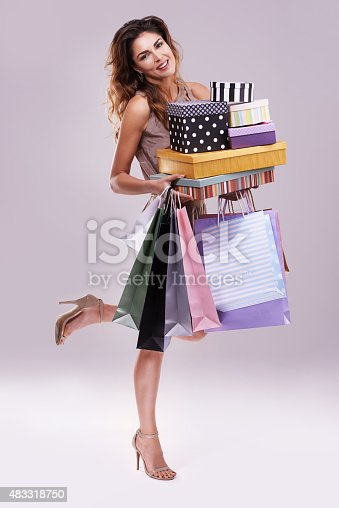 Studio shot of a woman holding shopping bags and boxes against a gray backgroundhttp://195.154.178.81/DATA/i_collage/pu/shoots/805376.jpg