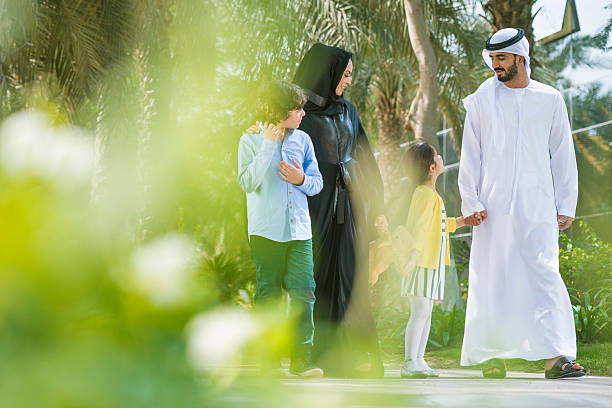 Spending Time Together Traditional Middle Eastern family walking in a park on a sunny morning. Mother and father are dressed in traditional clothes. They are talking and having fun. Copy space arabia stock pictures, royalty-free photos & images