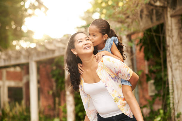 Spending time with daughter Mother giving piggyback ride to her loving daughter indonesian ethnicity stock pictures, royalty-free photos & images