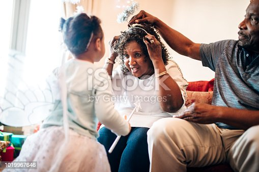 A little girl in an angel costume watches as her grandfather helps her grandmother put on a halo made of tinsel.