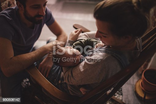 Photo of a young mother holding her newborn baby, while sitting in a rocking chair. Father is sitting next to them on the floor.